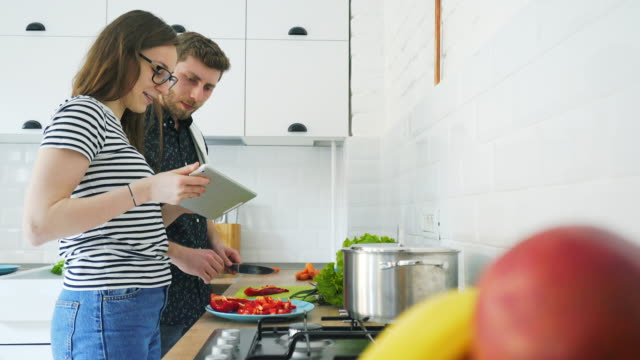 young couple cooking using a digital tablet. - cooking filmów i materiałów b-roll