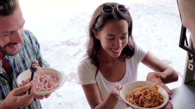 stockvideo's en b-roll-footage met jong (echt) paar klanten genieten van pasta die net besteld bij balie van food truck - foodtruck