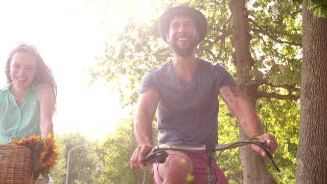 Young couple cycling happily together in Slow Motion