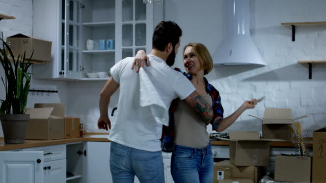 Young couple dancing in their new home