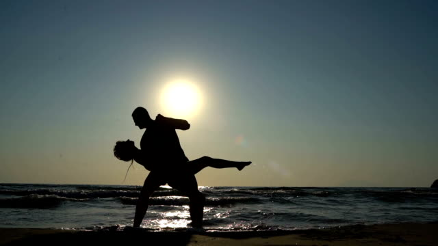 Young couple dancing salsa in the sea - video