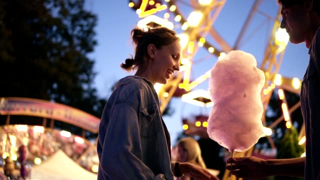 Young couple dating, meeting at the amusement park, male bring a cotton candy to her girlfriend. Kissing. Shine bright on the background. Low angle footage Young couple dating, meeting at the amusement park, male bring a cotton candy to her girlfriend. Kissing. Shine bright on the background. Low angle footage. cotton candy stock videos & royalty-free footage