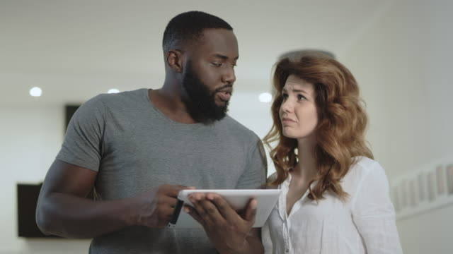 Young couple discussing at home kitchen together. Black man showing pictures