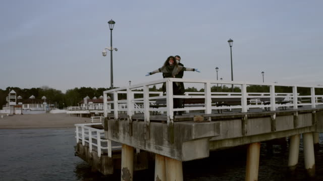 AERIAL: Young Couple Doing a 'Titanic' at the Edge of a Pier