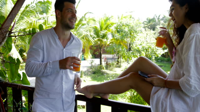 Young Couple Drink Juice Talking On Balcony In Hotel, Happy Man And Woman Communicating Outdoors In Morning video