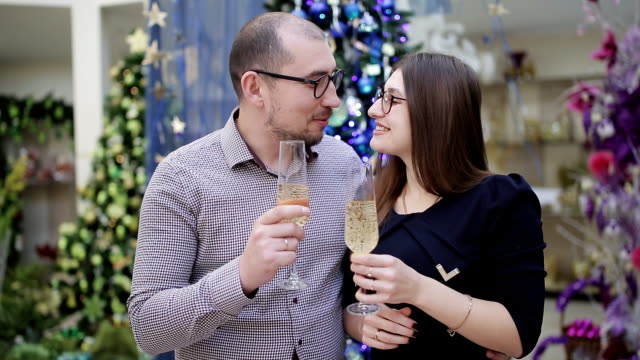 Young couple drinking champagne out of the glasses on the background of Christmas decorations and looking at the camera.