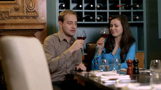 MS PAN Young couple drinking wine in restaurant video