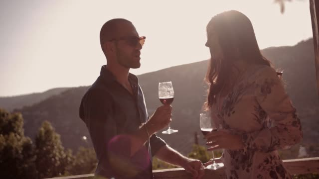 Young couple drinking wine on rustic balcony with mountain view Young couple drinking wine on vineyard winery rustic balcony with mediterranean mountains view winetasting stock videos & royalty-free footage