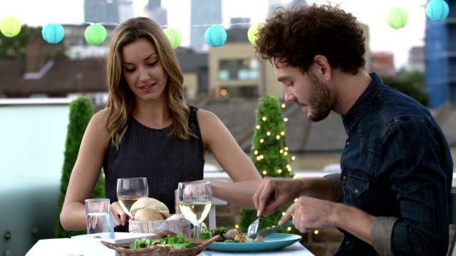 young couple eating meal on rooftop terrace - vitt vin glas bildbanksvideor och videomaterial från bakom kulisserna