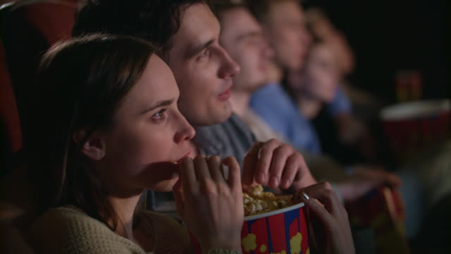young couple eating popcorn from one box. fiends couple watching movie - movies стоковые видео и кадры b-roll
