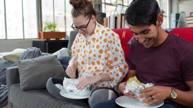 vídeos y material grabado en eventos de stock de pareja joven comiendo comida para llevar en casa - comida mexicana