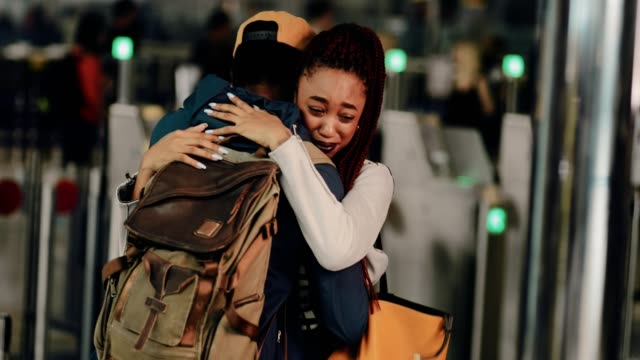 Young couple embracing and crying during emotional farewell at airport Young emotional boyfriend and girlfriend hugging and saying goodbye before separating at airport hug stock videos & royalty-free footage
