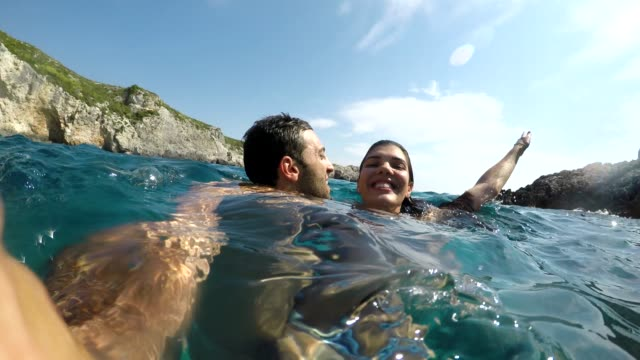Young couple embracing and taking a selfie at beach in Zakynthos Young couple embracing and taking a selfie at beach in Zakynthos greek islands stock videos & royalty-free footage