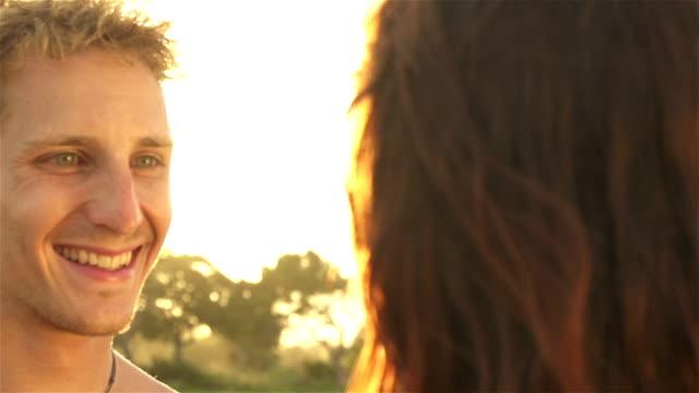 slow motion: young couple embracing at sunset - djurarm bildbanksvideor och videomaterial från bakom kulisserna