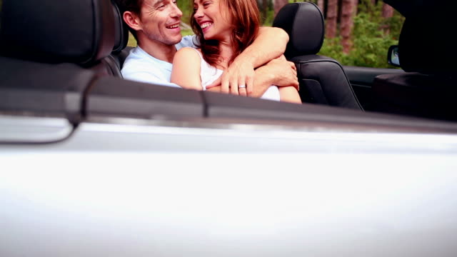 Young couple embracing in a convertible car