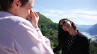 istock Young couple enjoy viewpoint of lake and mountains together, flirting 1319755925