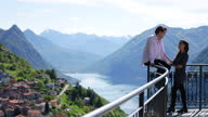 istock Young couple enjoy viewpoint of lake and mountains together, flirting 1319756676