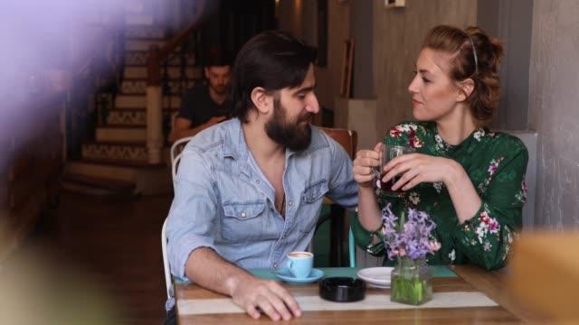 genç çift kahve dükkanında zevk - flört etmek stok videoları ve detay görüntü çekimi