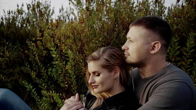 ungt par njuter av varandra sitter på gräsmattan i parken hösten - gå tillsammans bildbanksvideor och videomaterial från bakom kulisserna