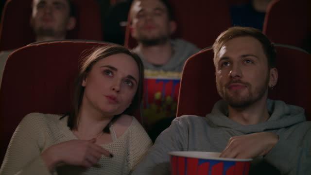 junges paar film im kino genießen. paar essen popcorn und film diskutieren - teenage friends sharing food stock-videos und b-roll-filmmaterial