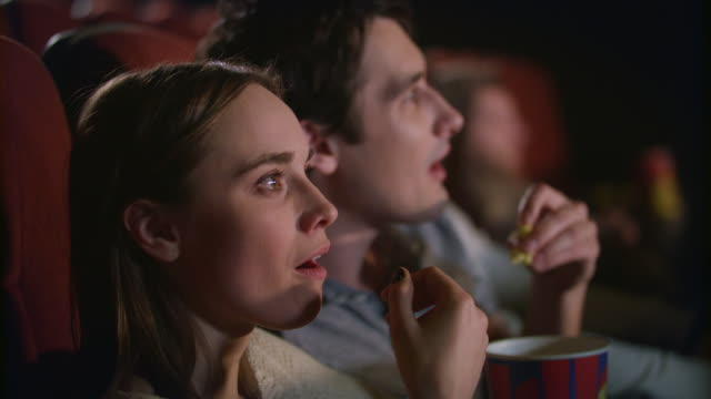 young couple enjoying film in cinema. couple eating popcorn and watching movie - свидание стоковые видео и кадры b-roll