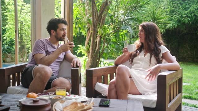 vídeos de stock e filmes b-roll de young couple enjoying relaxed weekend morning on home deck - mesa mobília