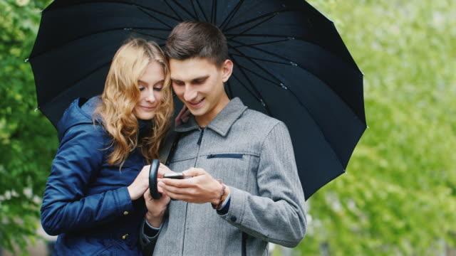 vídeos de stock e filmes b-roll de young couple enjoys a smartphone - standing under an umbrella, the rain. connected in any weather - guarda chuva