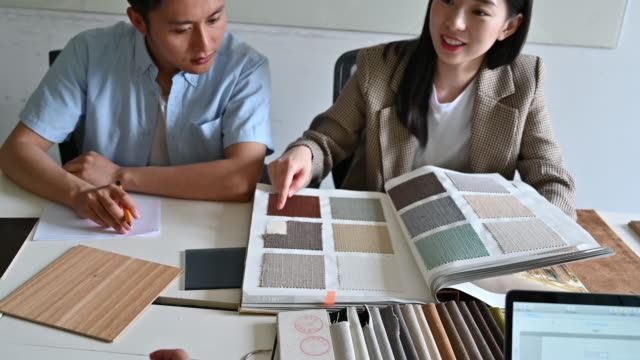 Young couple evaluating fabric swatches Smiling Chinese design team in their 20s sitting at conference table and discussing fabric and color swatch selections. fabric swatch stock videos & royalty-free footage