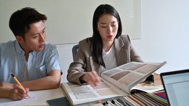 Young couple evaluating swatches Smiling Chinese design team in their 20s sitting at conference table and discussing fabric and color swatch selections. fabric swatch stock videos & royalty-free footage