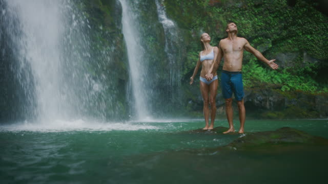 Young couple exploring waterfalls Young adventurous couple enjoying nature together in amazing waterfall pool in the jungle, summer adventures perfection stock videos & royalty-free footage
