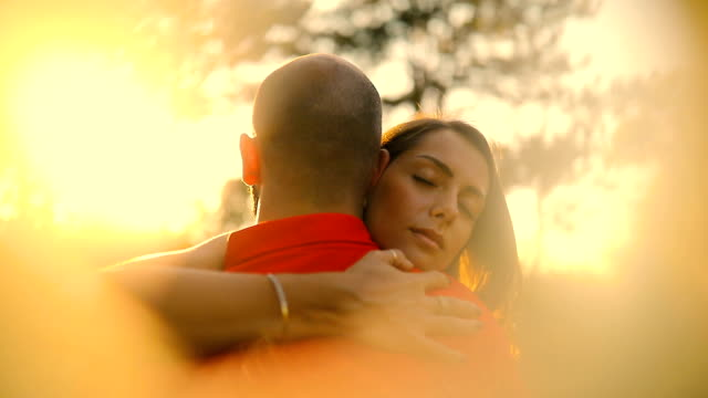Young couple expressing their love by the forest during beautiful sunset