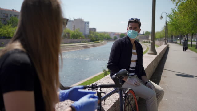 Young couple follow the rule of social distancing to avoid spread of coronavirus Charming modern young couple following the rules of social distancing while both wearing protective mask and gloves and communicate within two meters face mask videos stock videos & royalty-free footage