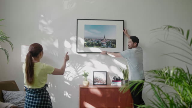 Young couple hanging a picture frame on the living room wall Video series of Japanese couple renovating their home during lockdown. hanging stock videos & royalty-free footage