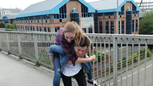 young couple have a piggy back ride on a bridge - teenagers stock videos and b-roll footage