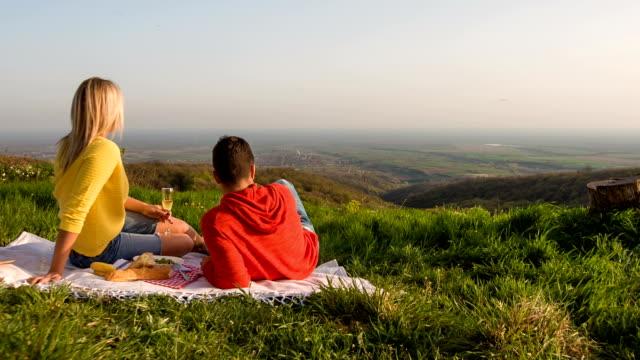 vídeos de stock e filmes b-roll de casal jovem tendo um piquenique na natureza - picnic