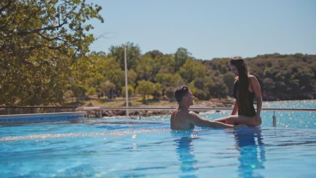 slo mo unga par har tillgiven stund i en pool. pool vid havet. infinity pool - flörta bildbanksvideor och videomaterial från bakom kulisserna