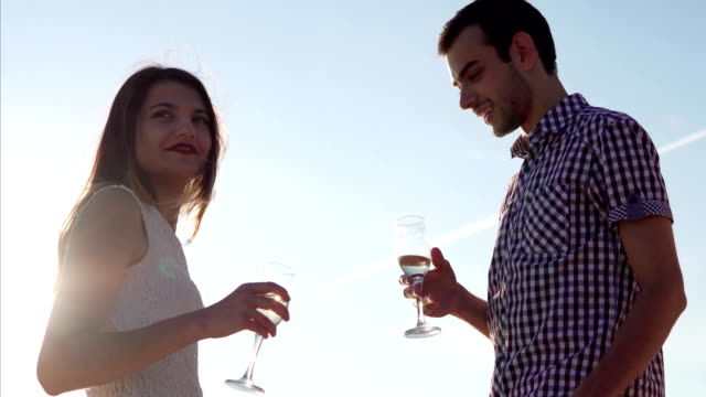 Young couple having drinks on the date. Scene against the sky at sunset video