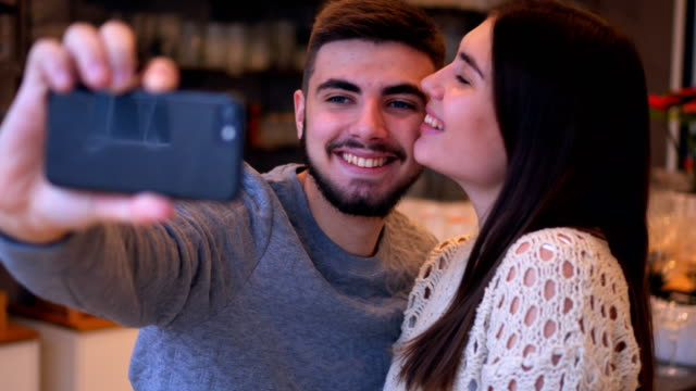 Young couple having fun while making selfie at cafe video