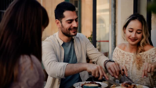 Pareja joven divirtiéndose con amigos en la cafetería tradicional - vídeo