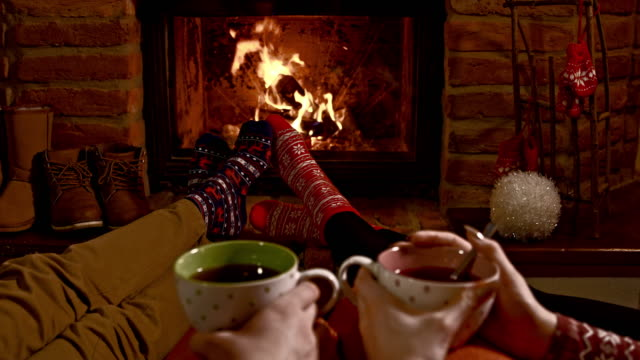 DS R/F Young couple having hot tea by the fireplace video
