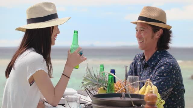 ビーチで昼食を持っている若いカップル。 ビデオ