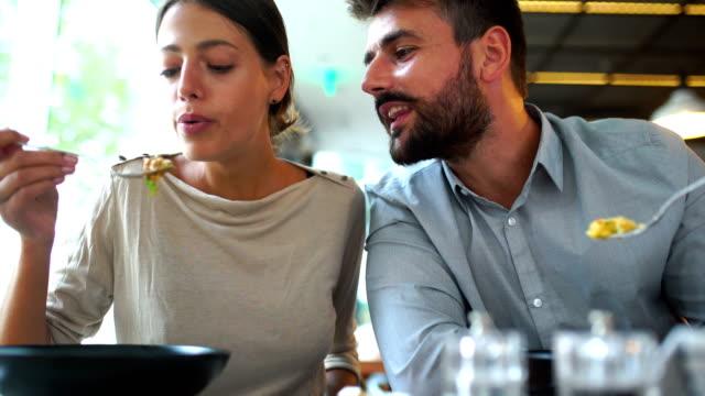 unga par att ha lunch på en restaurang. - fritidskläder bildbanksvideor och videomaterial från bakom kulisserna