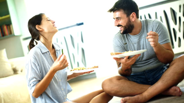 Young couple having lunch on the living room floor. Closeup of a mid 20's couple sitting on the living room floor and having some food. They are talking and laughing cross legged stock videos & royalty-free footage