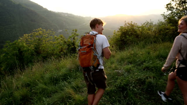 Young couple hike through meadow with backpacks at sunrise ビデオ