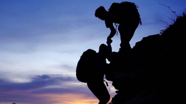 genç çift yürüyüşçüler gün batımında kayadağın zirvesinde zam tırmanma , takım çalışması için kavram , yardım , başarı, kazanan ve liderlik . - trust stok videoları ve detay görüntü çekimi