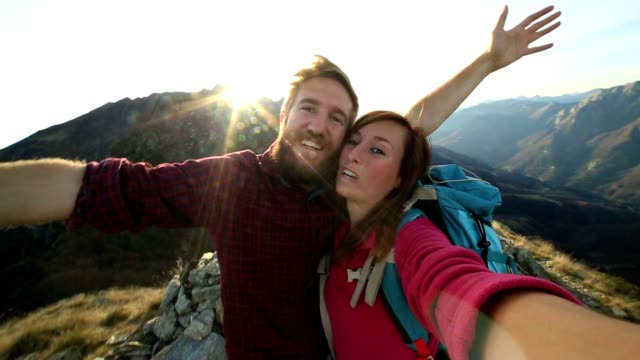 Young couple hikers taking selfie on mountain top Selfie at mountain top, young couple hiking in Switzerland take self portrait on mountain peak at sunset. young couple stock videos & royalty-free footage