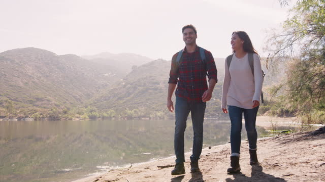 Young couple hiking by a mountain lake