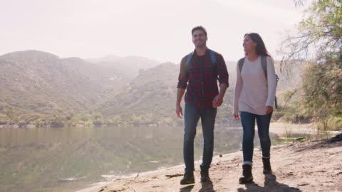 giovane coppia che escursioni in un lago di montagna - due persone video stock e b–roll