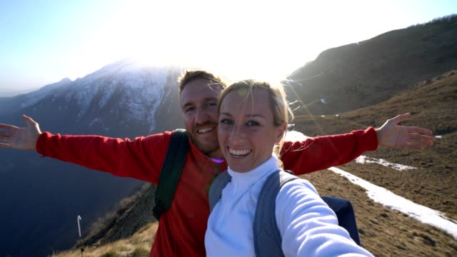 young couple hiking take selfie on mountain top - couple portrait caucasian video stock e b–roll