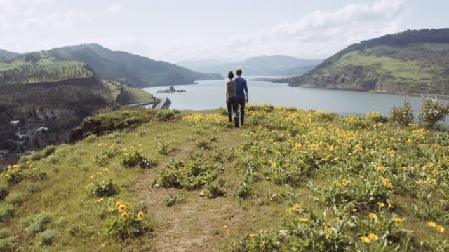 vídeos de stock e filmes b-roll de young couple hiking to cliff viewpoint - granadilha